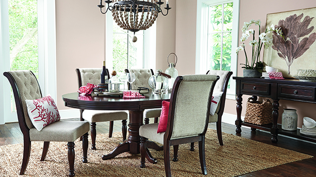 Dining room with matching white and brown chairs and coral accents.